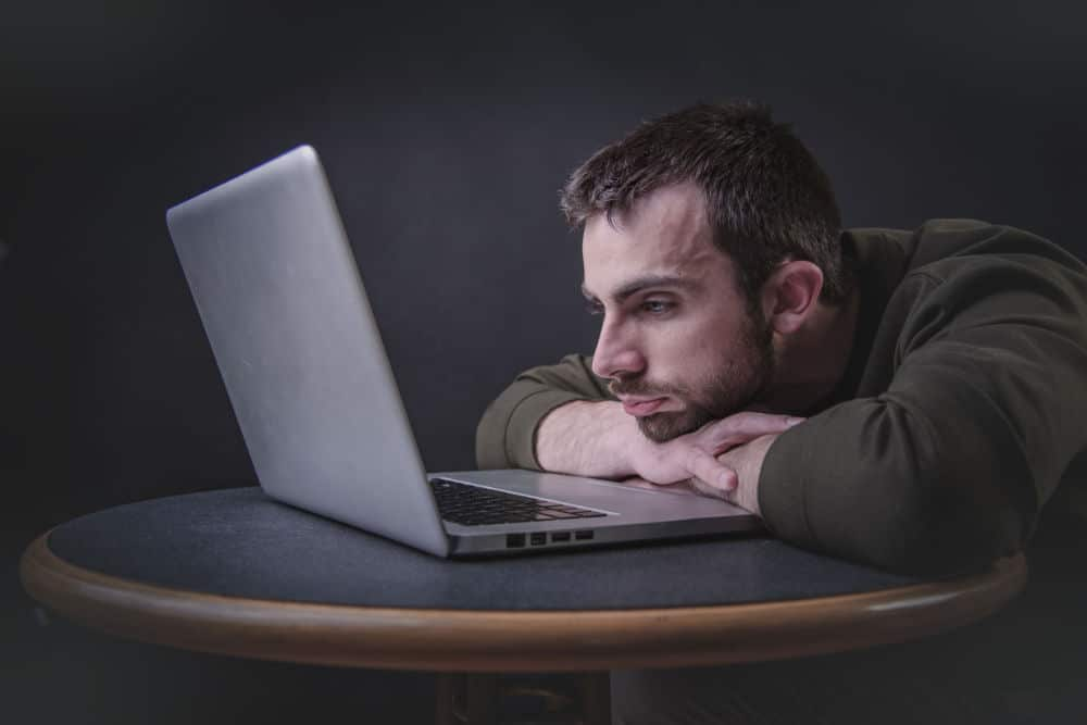 a guy staring at a laptop screen with arms crossed thinking how to get rid of writer's block