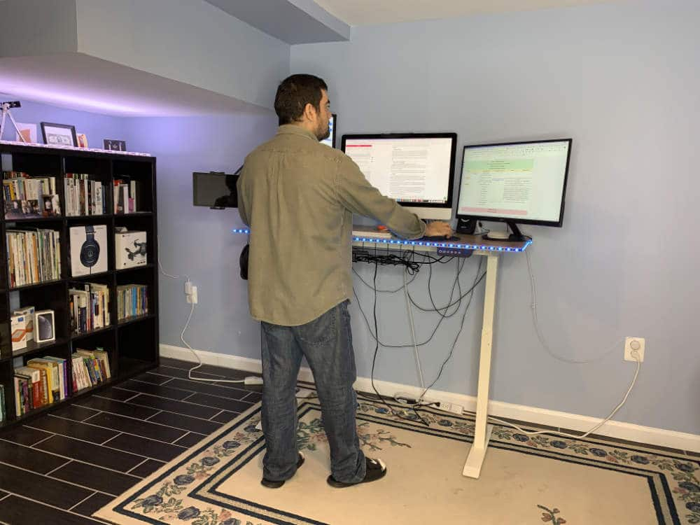a guy working at home standing up using his electric adjustable desk