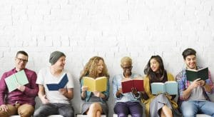 a group of people sitting down smiling and each reading book