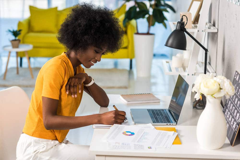 a young woman at a desk emulating someone else's writing style